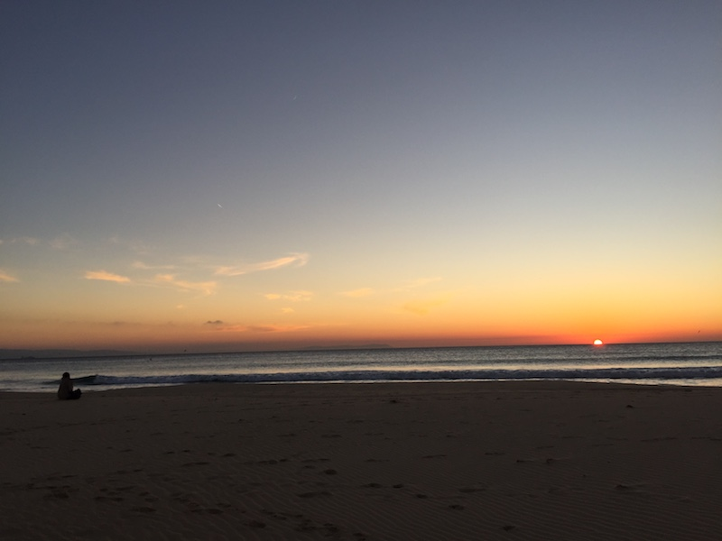 image from Tarifa's beach during sunset. A girl is sitting on the beach and watches the sky and the coast of Morocco.