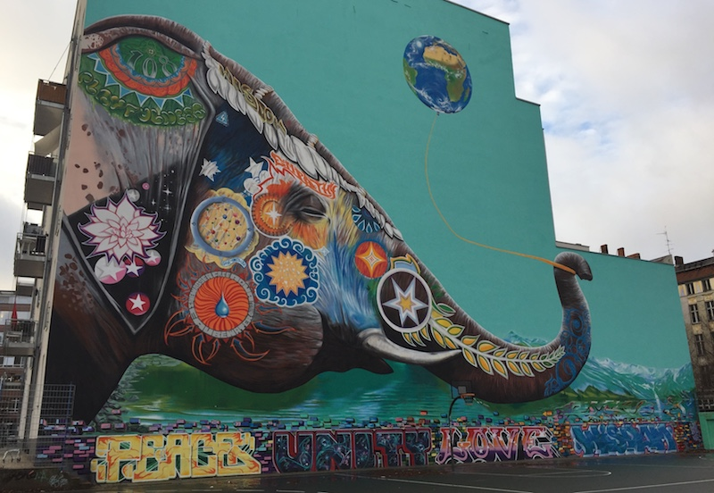 Image of graffiti done on the wall of a building in Berlin showing an elefant holding a ballon with the shape of the world