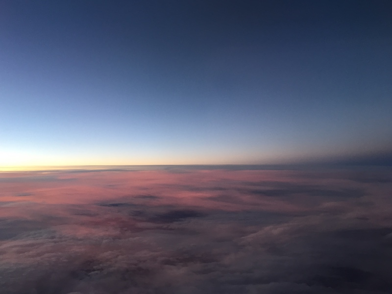 Image of sky taken from plane showing pink clouds and transition between day and night